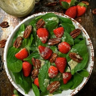 Spinach Salad with Strawberries and Pecans in a white bowl with poppy seed dressing.