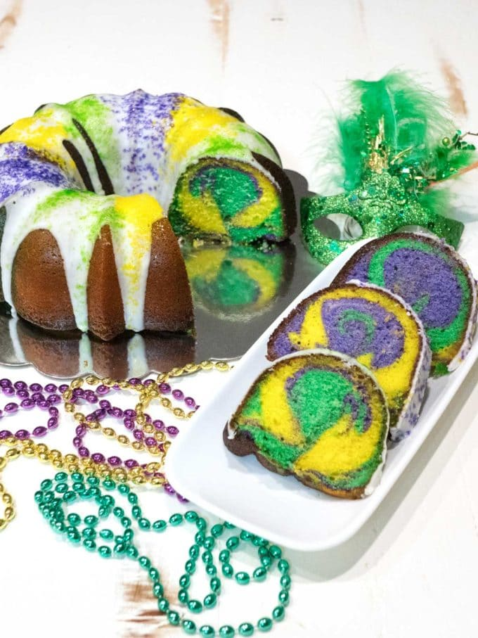 Lemon Bliss Bundt Cake with with slices showing yellow, green and purple swirled throughout the cake..