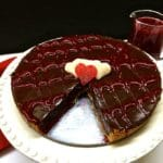 Chocolate Raspberry Tart with a slice cut out topped with raspberry sauce