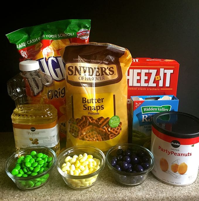 A bag of mini pretzels, Cheez-its, peanuts, vegetable oil, bugles, and multicolored candy.