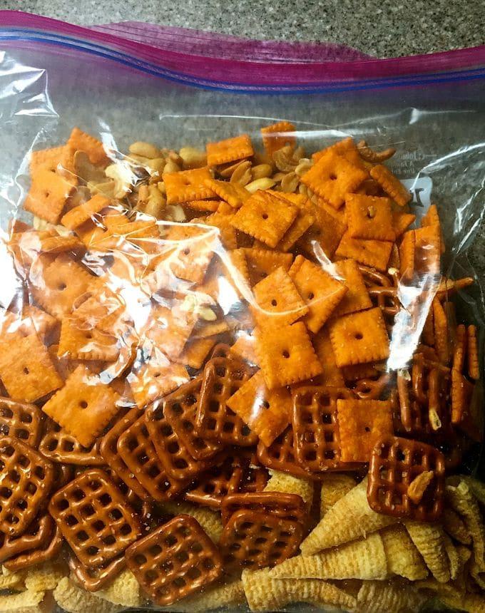A gallon size Ziploc bag with Cheez-its, pretzels and bugles.