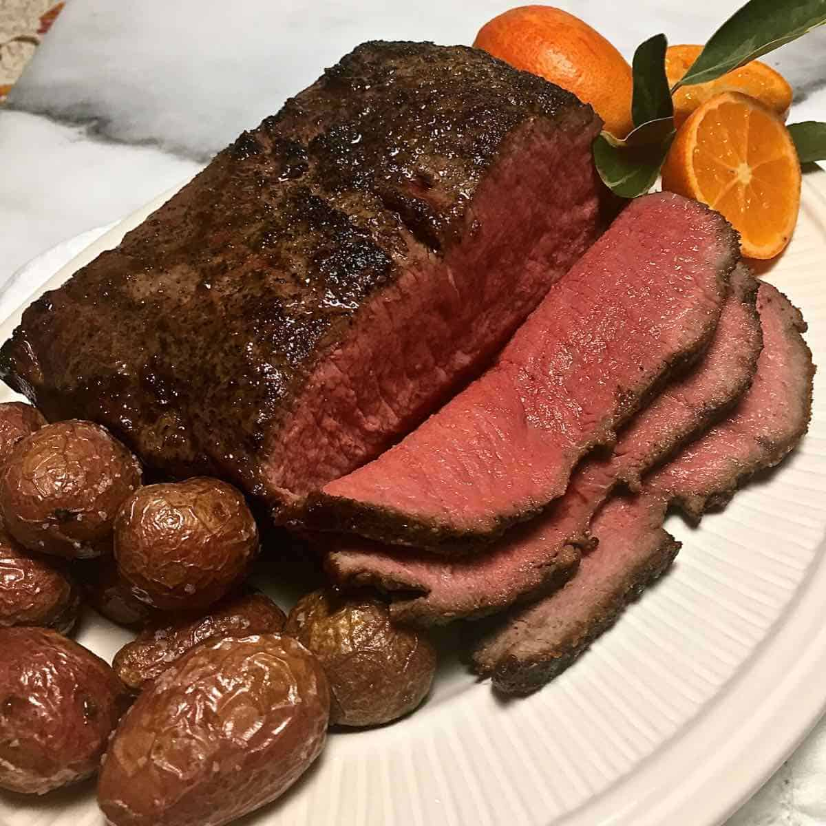 Sliced New York Strip Roast with small potatoes on a white plate.