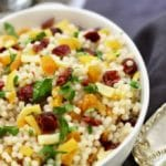 Pearl Couscous with Preserved Lemon in a bowl with cranberries, apricots, parsley, and pistachios in a white serving bowl
