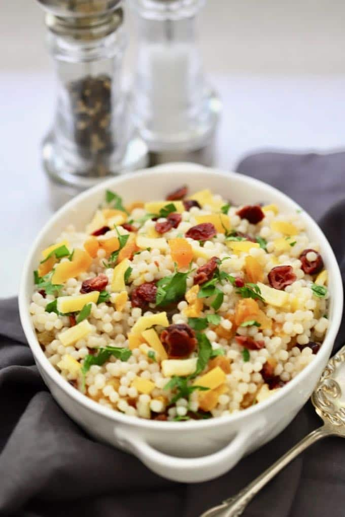 Pearl Couscous with Preserved Lemon in a white serving dish with salt and pepper shakers in the background
