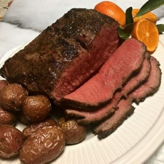 Skillet New York Strip Roast sliced with potatoes and garnished with oranges.