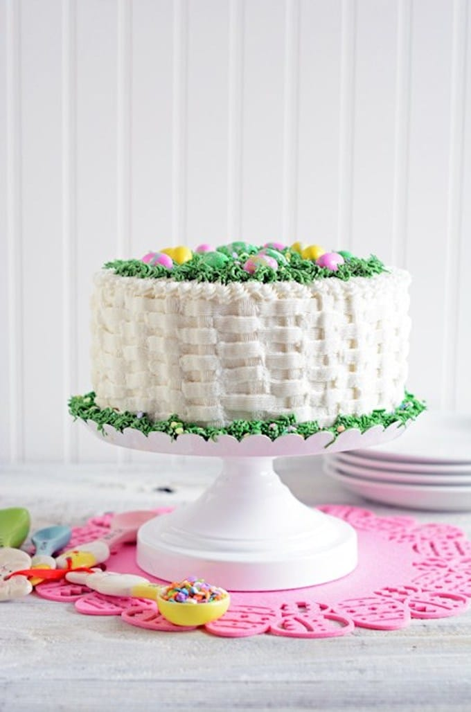 A beautiful cake with white icing piped in a basket weave pattern topped with candy Easter eggs.