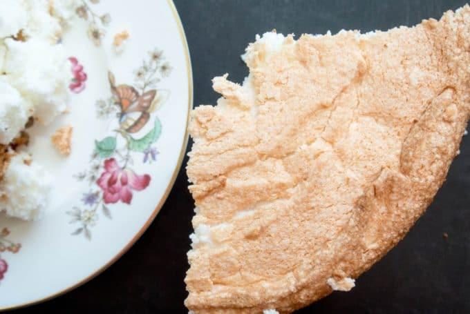 A piece of angle food cake on a flowered cake plate.