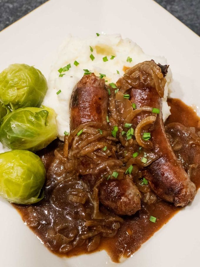 An Irish dish of Bangers and Mash with Onion Gravy on a plate with brussel sprouts