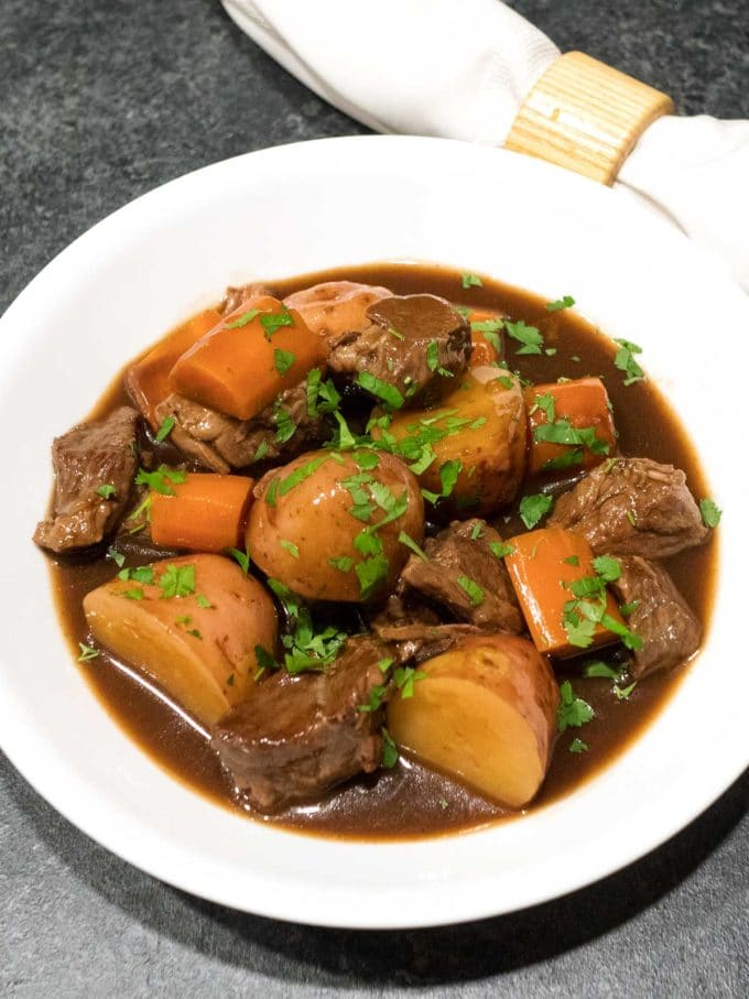 Slow Cooker Irish Guinness Beef Stew in a white bowl with cut up potatoes and carrots