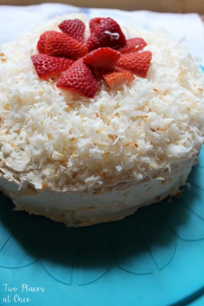 A coconut cake topped with coconut and sliced strawberries.