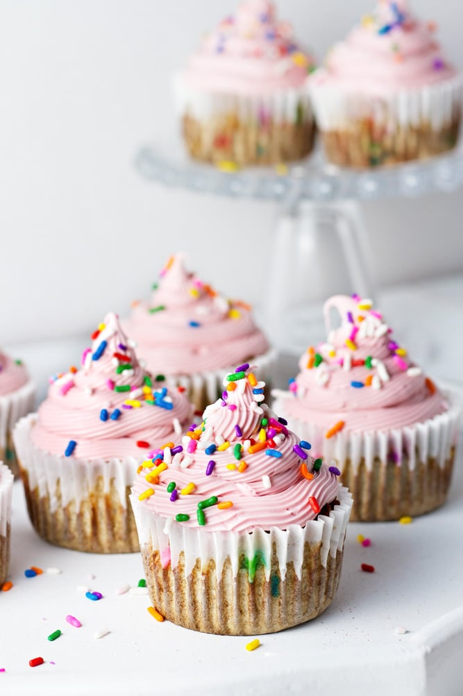 Cupcakes topped with pink icing and multicolor sprinkles.