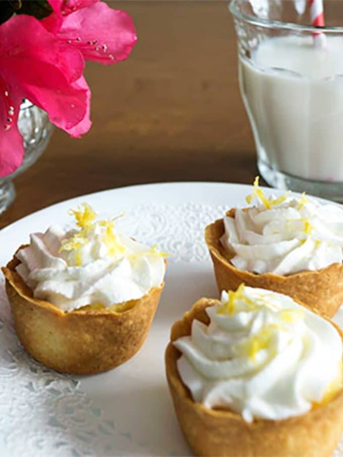 Three tartlets with lemon filling topped with whipped cream and lemon zest.