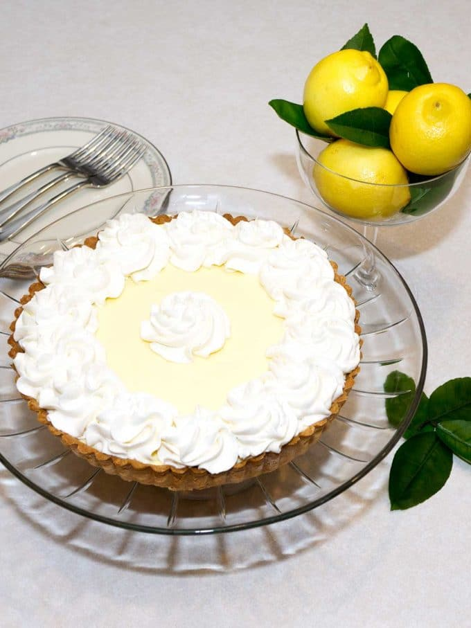 A french cream tart on a clear glass plate topped with whipped cream.