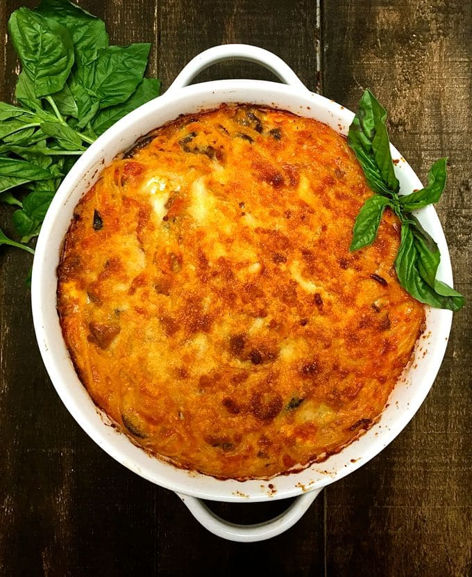 A white baking dish full of Easy Baked Spaghetti Pie and garnished with fresh basil ready to serve