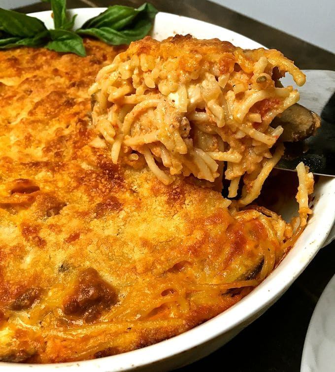 Easy Baked Spaghetti Pie Casserole in a white baking dish with a serving spoon
