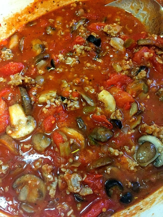 A photo of tomato sauce being added to a skillet with mushrooms and sausage for Easy Baked Spaghetti Pie Casserole