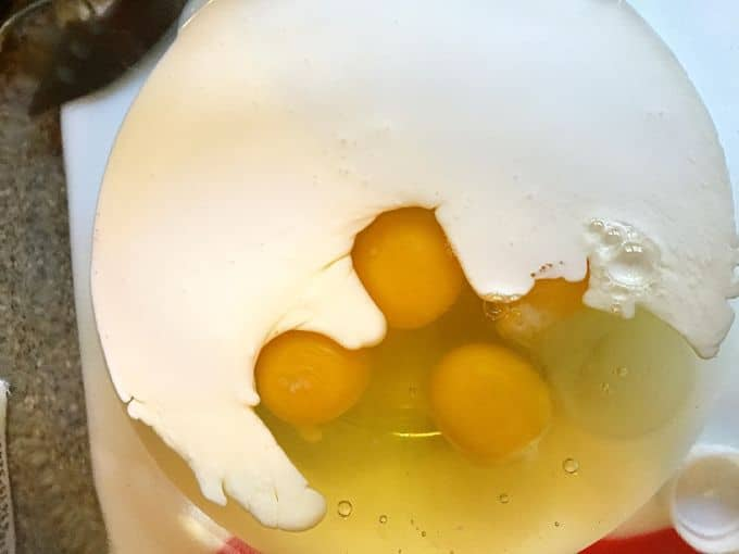 Adding heavy cream and eggs to a clear glass bowl to add to the other Easy Baked Spaghetti Pie Casserole Ingredients