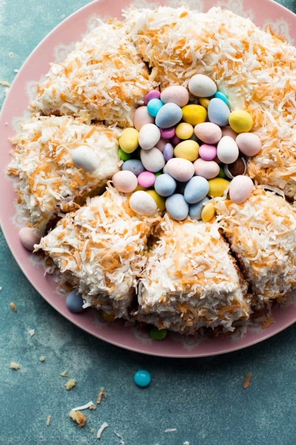 A cake topped with coconut and Easter candy.