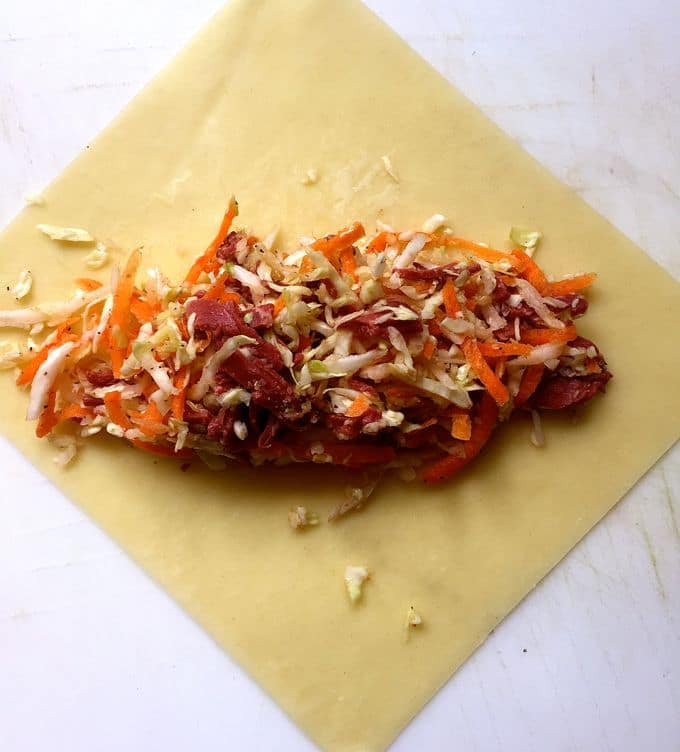 A spoonful of cabbage and corned beef in the center of an egg roll wrapper.