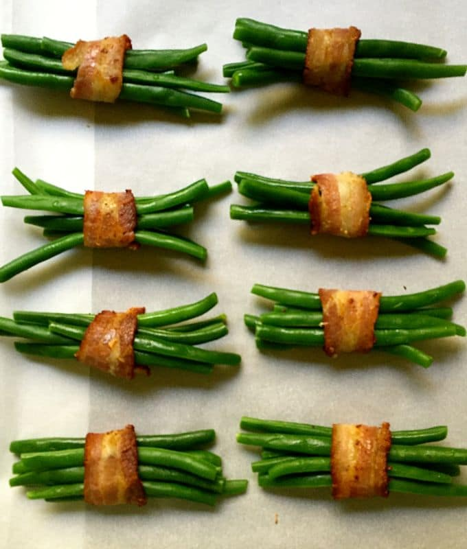 Green Bean Bundles Wrapped in Bacon on a parchment paper lined baking sheet ready for the oven.