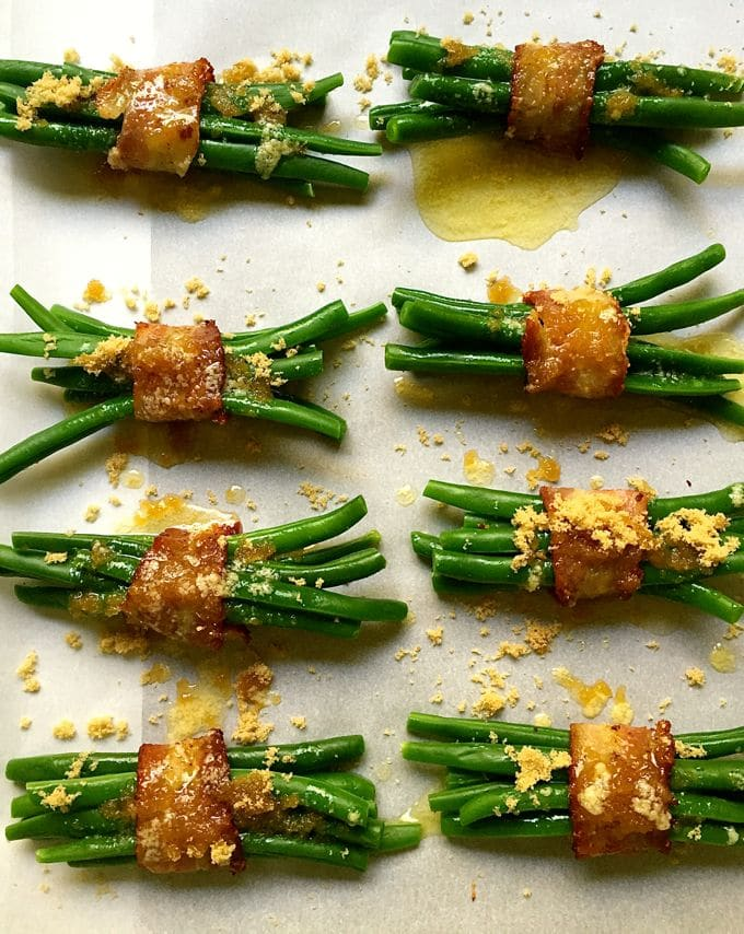 Green Bean Bundles Wrapped in Bacon with brown sugar and butter topping on a baking sheet ready for the oven.