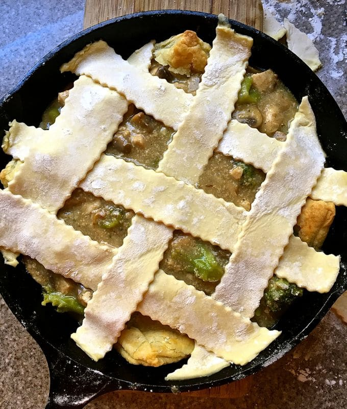 Chicken pot pie with lattice pastry in a cast iron skillet.