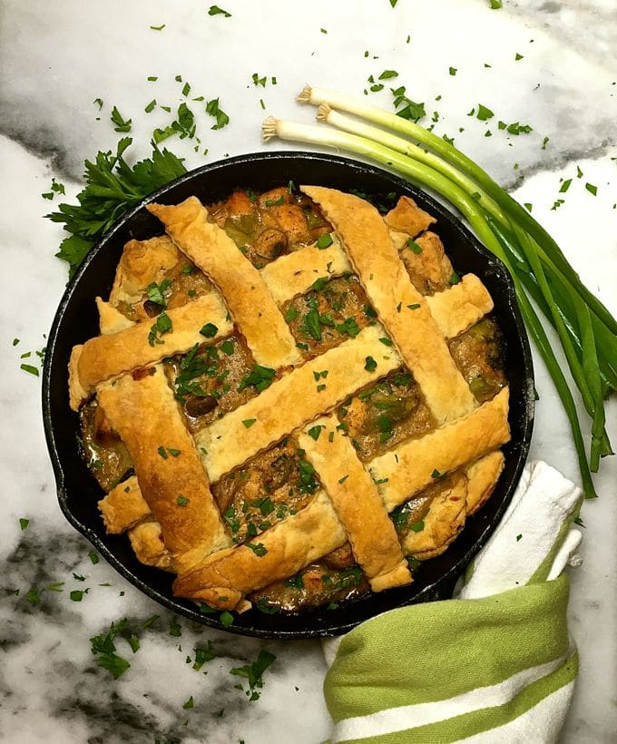 Chicken pot pie with lattice pastry garnished with parsley.