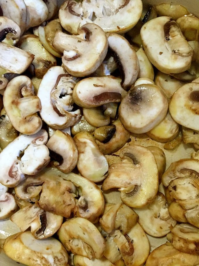 Mushrooms sautéing in a pan.