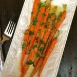Roasted Carrots with Lemon Vinaigrette garnished with parsley on a white serving platter.