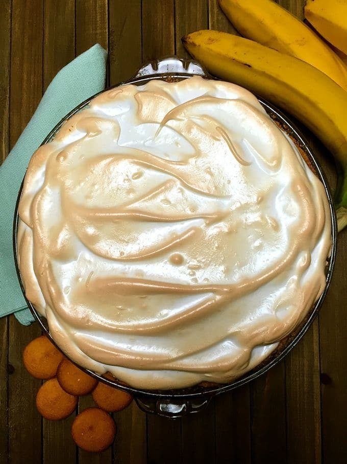 Southern Banana Pudding Pie in a pie plate with bananas and kumquats next to it.