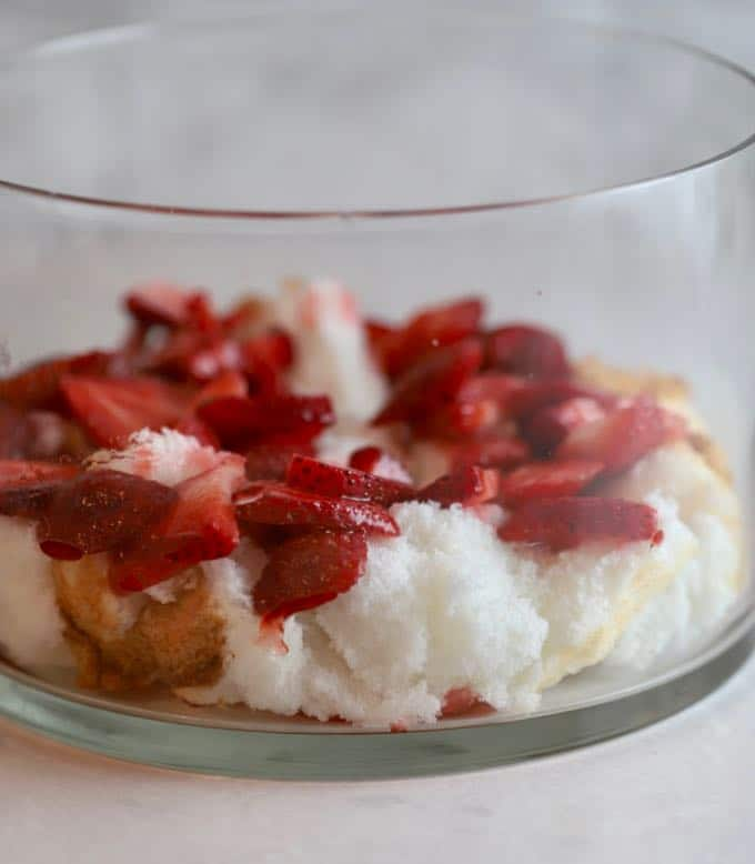 A layer of strawberries and angel food cake in a trifle dish for Strawberry Trifle with Angle Food Cake