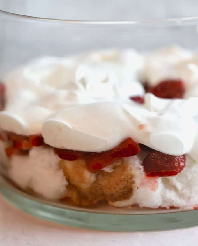 Whipped cream, strawberries, and angel food cake in a trifle dish for Strawberry Trifle with Angle Food Cake