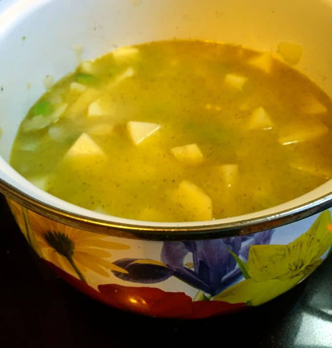 Potatoes, celery and onions cooking in chicken broth in a large colorful pot for Traditional Irish Potato Soup