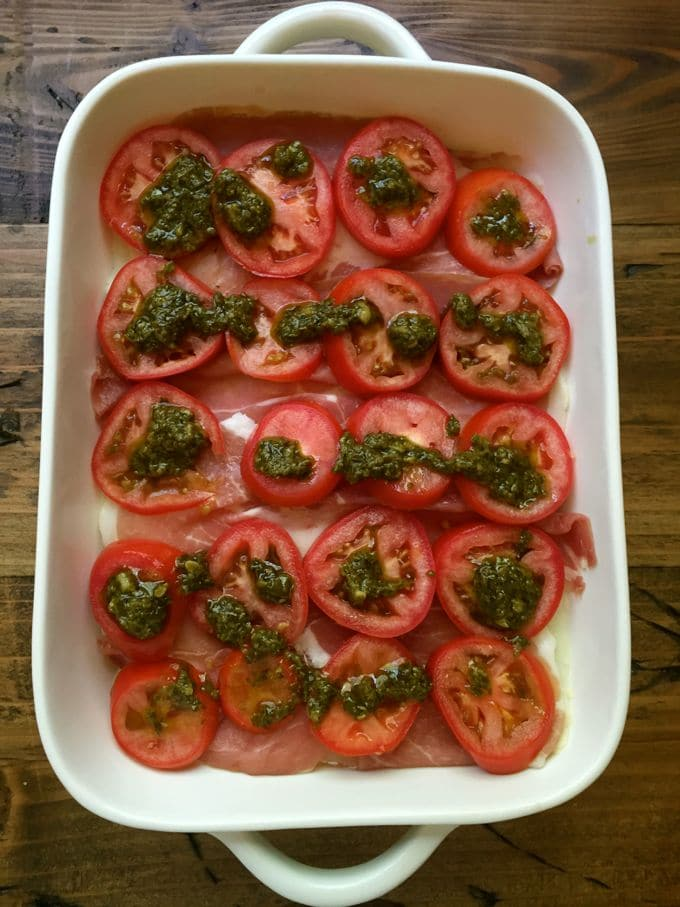 Sliced tomatoes and pesto on top of prosciutto in a casserole dish.