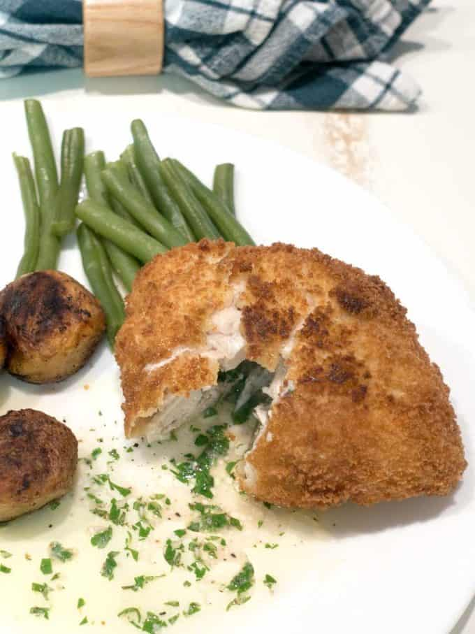 Chicken Kiev on a white plate with green beans and small potatoes.