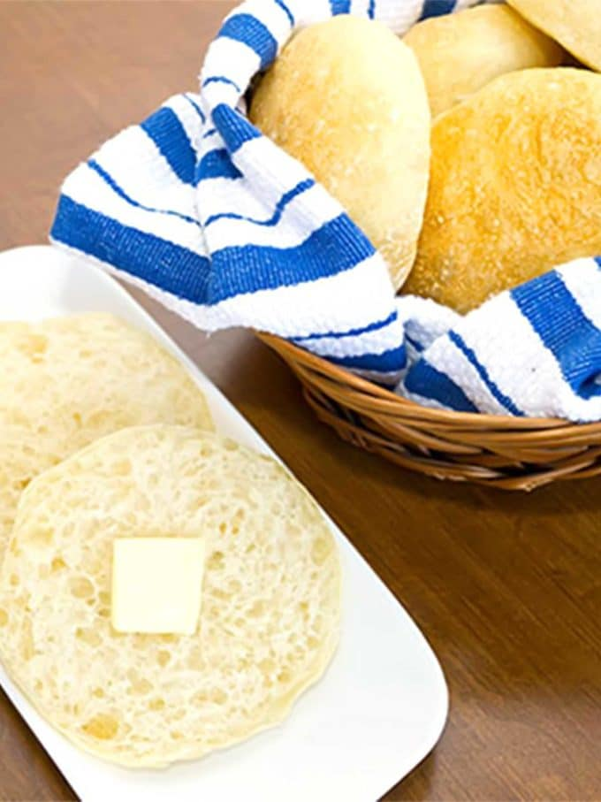 A small basket of french bread rolls wrapped in a blue striped napkin.