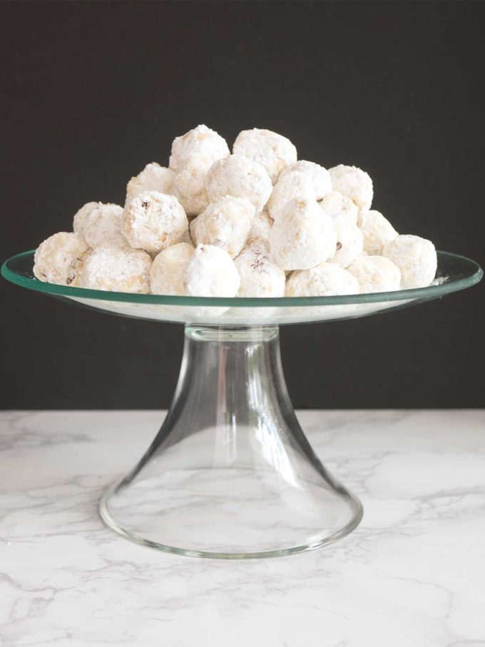 A clear glass serving dish full of Mexican Wedding Cookies covered with powdered sugar