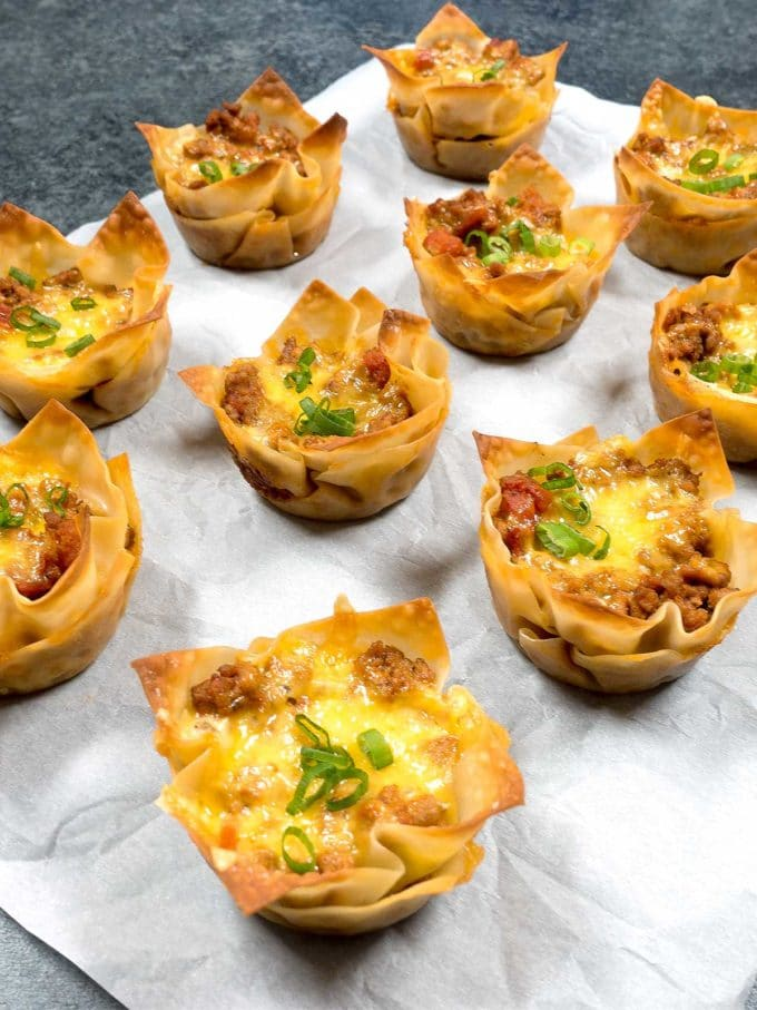 Tasty Taco Cups on a sheet of parchment paper topped with cheese and chives