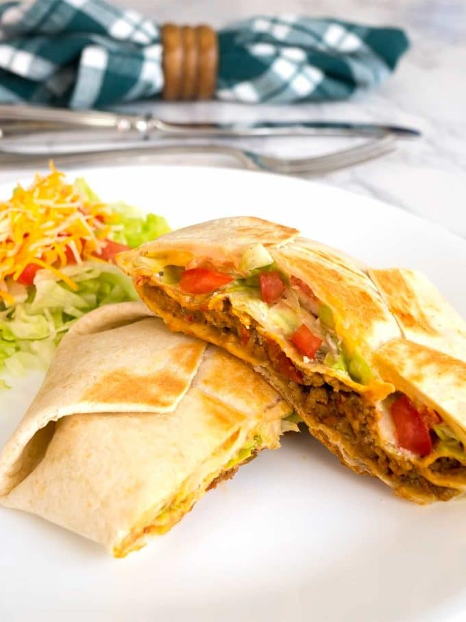 Tasty 7 Layer Quesadilla Wrap cut in half showing the filling with extra cheese, tomatoes and lettuce