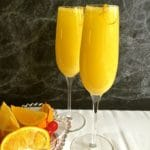 Two champagne flutes full of mimosas.