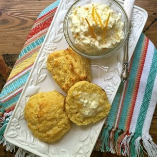 A plate of cornmeal biscuits and a small bowl of orange butter.