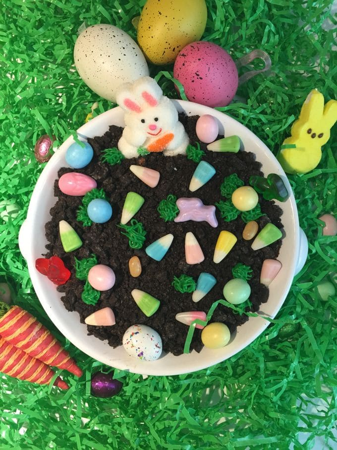 A bowl full of cheesecake dip topped with crumbled Oreos and Easter candy.