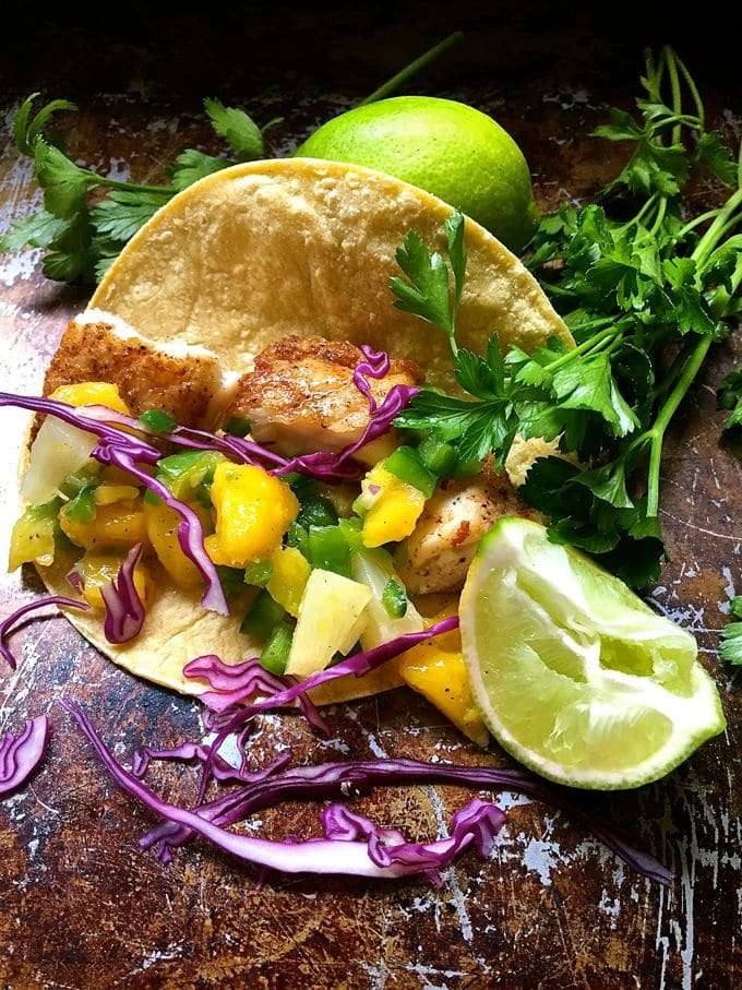 Fish Tacos with Mango Salsa on a baking sheet with mango chunks and cabbage spilling out of the taco