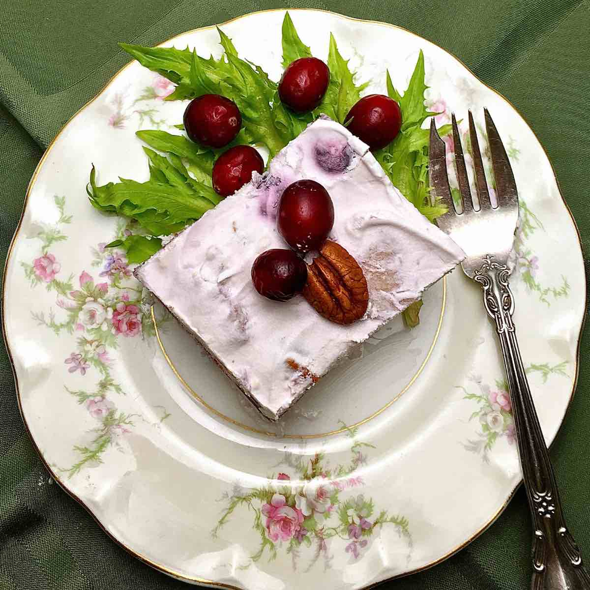 A square of frozen fruit salad garnished with cherries and nuts.