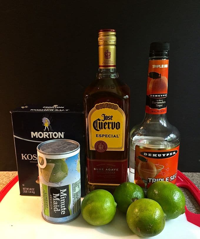 Margarita ingredients including tequila, triple sec, limeade and limes on a kitchen counter.