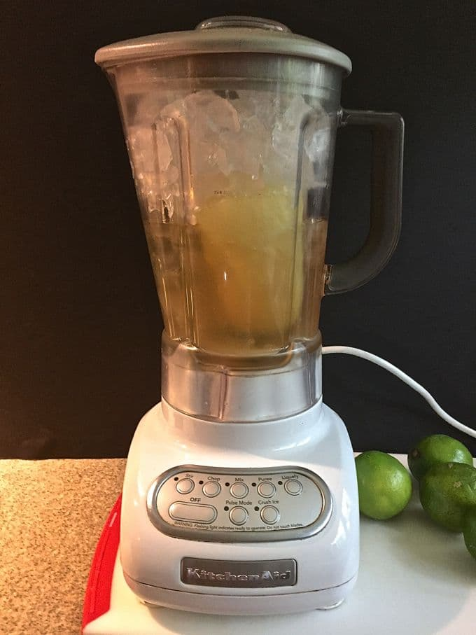 A blender full of ice and the ingredients to make frozen margaritas.
