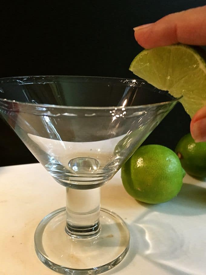 Rubbing a lime on a margarita glass so the salt will stick.
