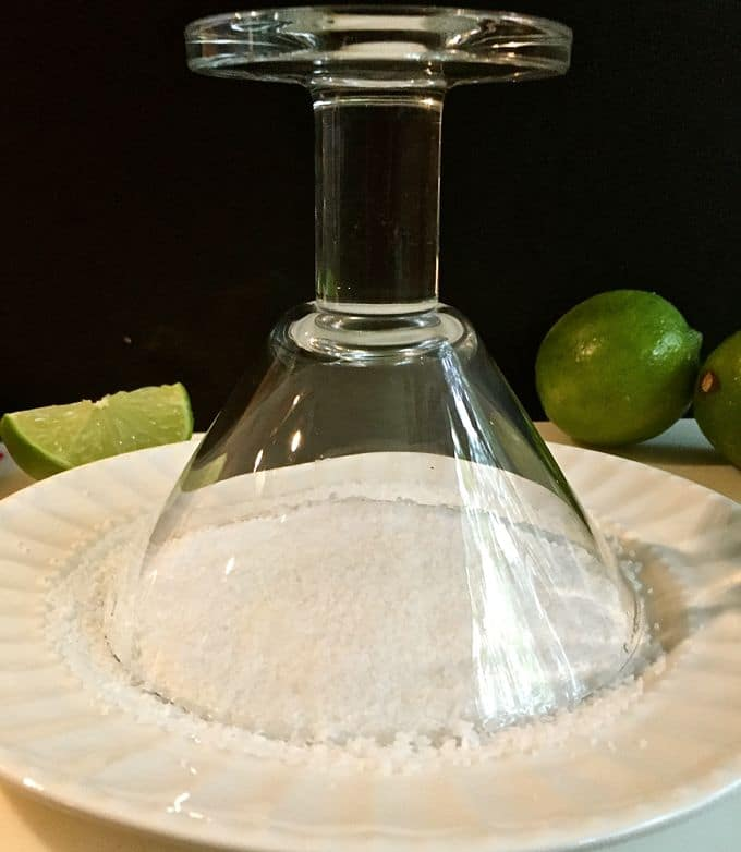 Dipping a margarita glass in a plate full of salt.
