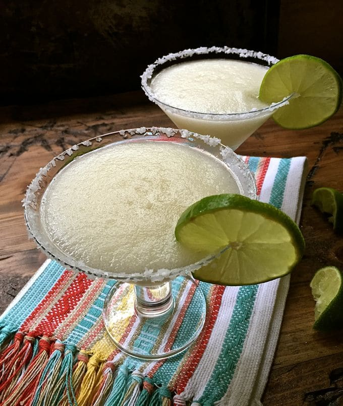 Two glasses full of Jack's Ultimate Frozen Margaritas garnished with lime slices