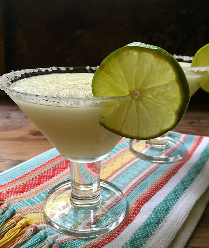 Jack's Ultimate Frozen Margaritas on a striped towel in a margarita glass rimmed with salt and garnished with a lime slice